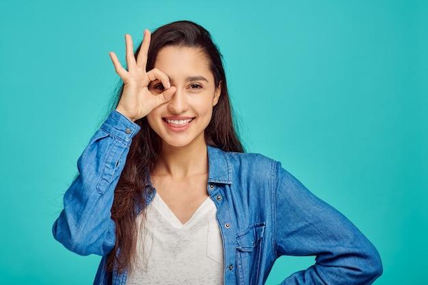 Mulher jovem bonita mostra ok dign, parede azul, emoção positiva. expressão facial, pessoa do sexo feminino olhando para a câmera no estúdio, conceito emocional, sentimentos
