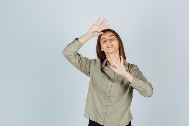 Mulher jovem bonita mostrando gesto de recusa, fechando os olhos na camisa e parecendo envergonhada. vista frontal.