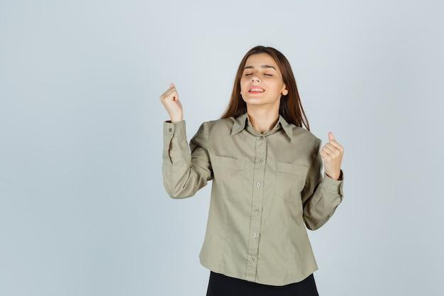 Mulher jovem bonita na camisa, saia, mostrando o gesto do vencedor e olhando feliz, vista frontal.