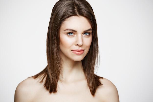 Mulher jovem bonita nua com natural compõem sorrindo. cosmetologia e spa. tratamento facial.