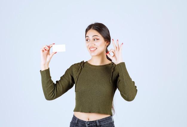 Mulher jovem bonita olhando para o cartão em branco e dando sinal de ok.