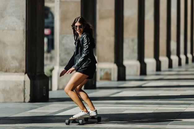 Mulher jovem bonita patinadora andando em seu longboard na cidade.