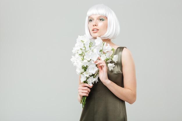 Mulher jovem bonita pensativa com buquê de flores