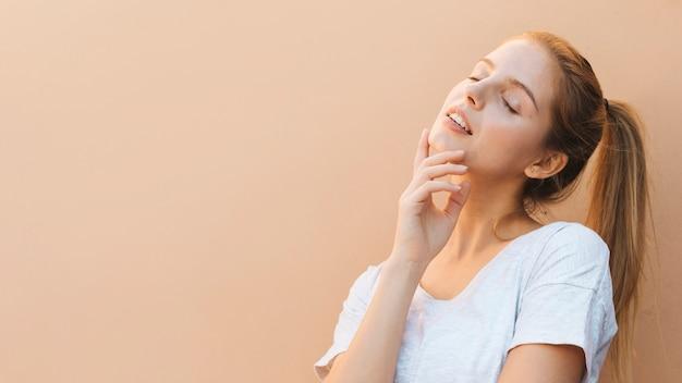 Mulher jovem bonita pensativa com olho fechado contra o pano de fundo bege