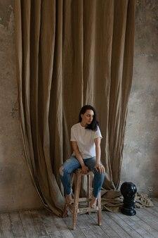 Mulher jovem bonita perto de estúdio fotográfico com luz natural