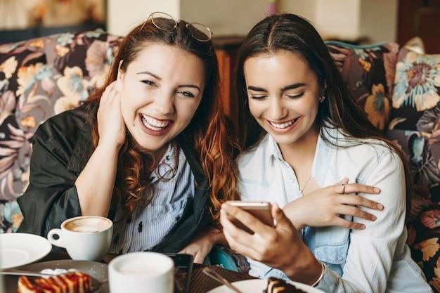 Mulher jovem bonita plus size olhando para a câmera rindo enquanto a amiga está olhando para um smartphone rindo enquanto está sentada em uma cafeteria.
