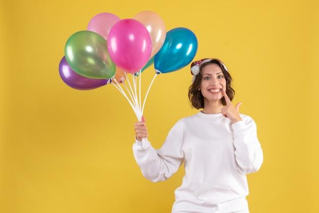 Mulher jovem bonita segurando balões na mesa amarela natal ano novo cor de frente