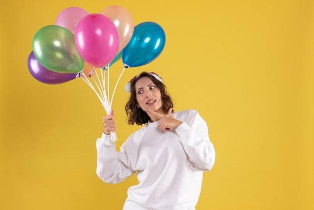 Mulher jovem bonita segurando balões na mesa amarela natal mulher cor de ano novo, vista frontal