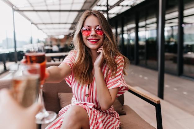 Mulher jovem bonita segurando coquetel e sorrindo num dia de verão. rapariga loira em êxtase de óculos cor de rosa relaxando com um copo de vinho no fim de semana.
