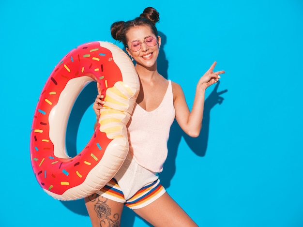 Mulher jovem bonita sexy sorridente hipster em óculos de sol. com colchão inflável donut lilo ... mostra sinal de paz