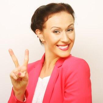 Mulher jovem bonita sorridente feliz mostrando dois dedos ou gesto de vitória