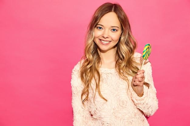 Mulher jovem bonita sorridente hipster em roupas da moda no verão. mulher despreocupada sexy posando perto de parede rosa. modelo positivo comendo pirulito