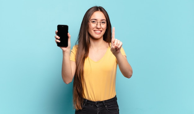 Mulher jovem bonita sorrindo e parecendo amigável, mostrando o número um ou primeiro com a mão para a frente, em contagem regressiva