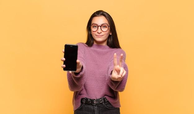 Mulher jovem bonita sorrindo e parecendo feliz, despreocupada e positiva, gesticulando vitória ou paz com uma mão. conceito de tela do telefone