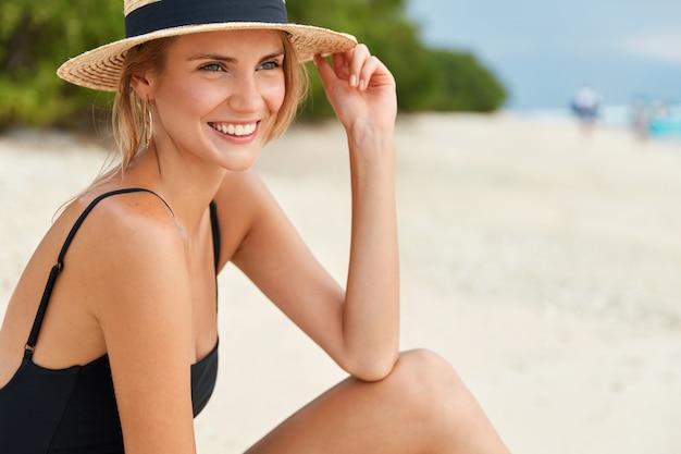 Mulher jovem bonita usa maiô, tem um sorriso positivo no rosto e pele bronzeada fresca, admira um bom descanso na praia do oceano. sol brilhante, verão, calor, viagens e conceito de descanso. relaxamento country exótico
