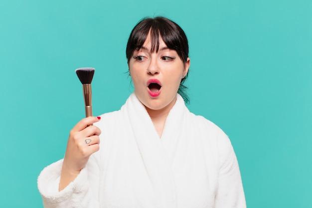 Mulher jovem bonita vestindo roupão de banho expressão de medo e maquiagem