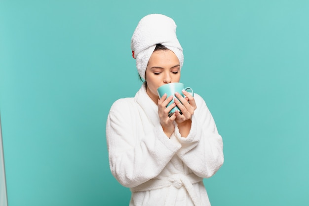 Mulher jovem bonita vestindo roupão de banho expressão feliz e segurando uma caneca de café
