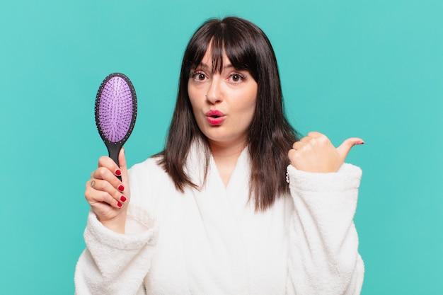 Mulher jovem bonita vestindo um roupão de banho com expressão de surpresa e segurando uma escova de cabelo