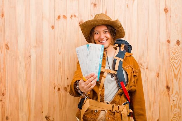 Mulher jovem bonita viajante com bilhetes de um cartão de embarque