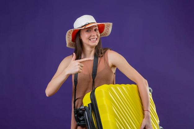 Mulher jovem bonita viajante no chapéu de verão com mala amarela e câmera positiva e feliz sorrindo apontando com o dedo para o lado ao longo da parede roxa