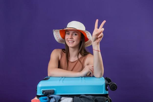 Mulher jovem bonita viajante no chapéu de verão com mala cheia de roupas positivas e felizes sorrindo alegremente otimistas mostrando sinal de vitória ou número dois sobre parede roxa
