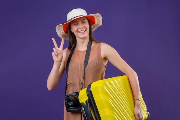 Mulher jovem bonita viajante no chapéu do verão com mala amarela e câmera positiva e feliz sorrindo alegremente mostrando sinal de vitória ou número dois sobre parede roxa