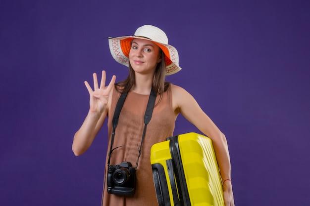 Mulher jovem bonita viajante no chapéu do verão com mala amarela e câmera positiva e feliz sorrindo mostrando o número três sobre parede roxa