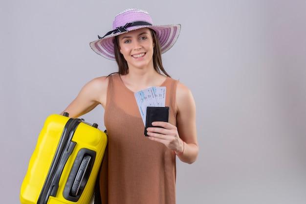Mulher jovem bonita viajante no chapéu do verão segurando a mala amarela e bilhetes sorrindo com cara feliz sobre parede branca