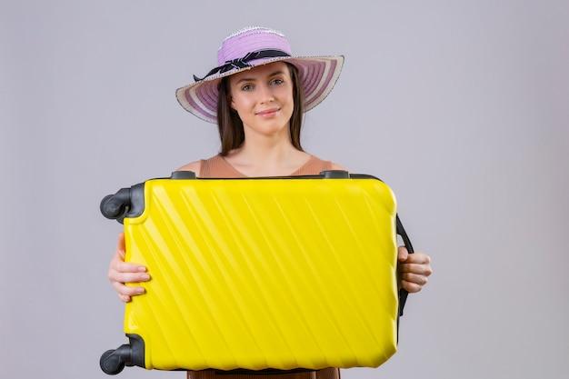 Mulher jovem bonita viajante no chapéu do verão segurando a mala amarela, sorrindo com cara feliz sobre parede branca