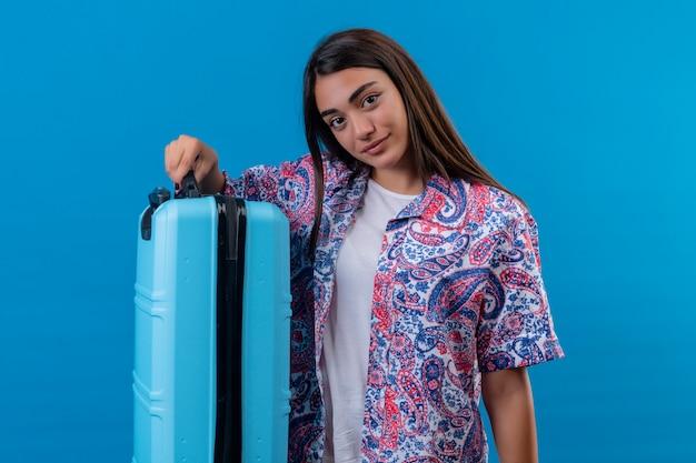 Mulher jovem bonita viajante segurando a mala azul com sorriso confiante sobre parede azul