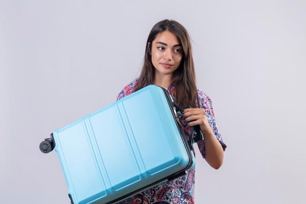 Mulher jovem bonita viajante segurando a mala azul, olhando de lado com um sorriso confiante sobre parede branca