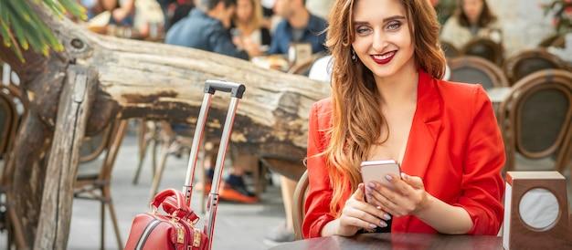 Mulher jovem bonita viajar com smartphone sentado à mesa olhando para a câmera no café ao ar livre