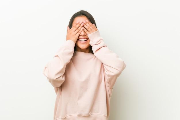 Mulher jovem bonito adolescente hispânico cobre os olhos com as mãos, sorri amplamente esperando por uma surpresa.
