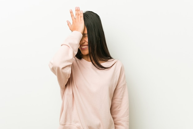 Mulher jovem bonito adolescente hispânico esquecendo algo, batendo na testa com a palma da mão e fechando os olhos.