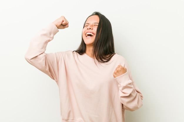 Mulher jovem bonito adolescente hispânico, levantando o punho após uma vitória, vencedor.