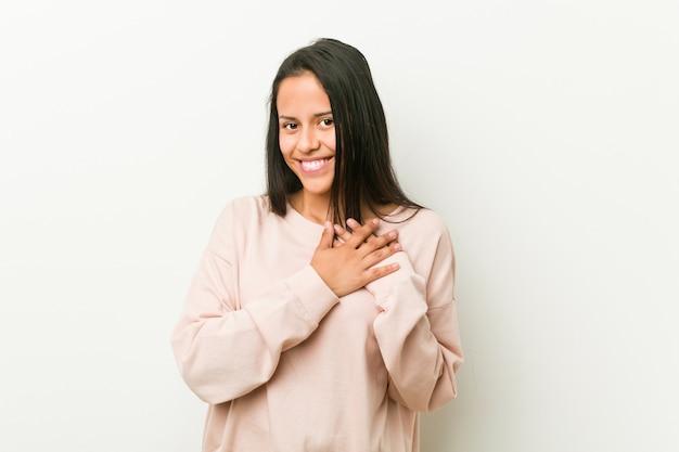 Mulher jovem bonito adolescente hispânico tem expressão amigável, pressionando a palma da mão no peito