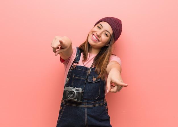 Mulher jovem bonito fotógrafo alegre e sorridente apontando para a frente