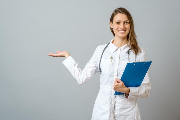 Mulher jovem bonito médico apresentando e apontando