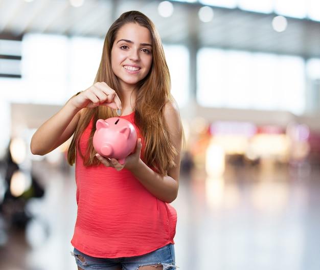 Mulher jovem bonito poupança com um banco piggy