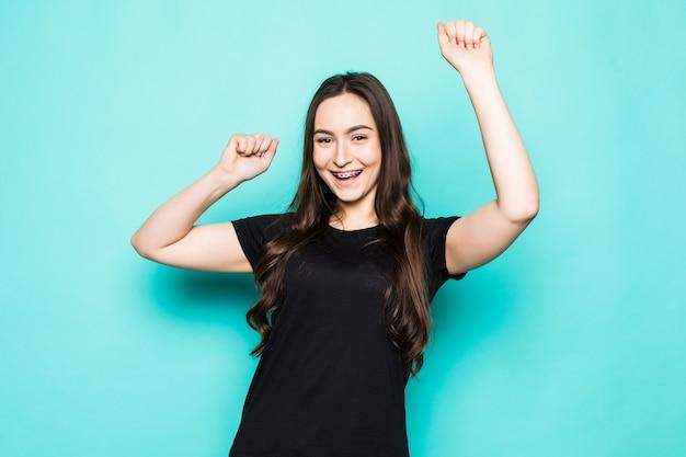 Mulher jovem, braço, mão, palma, punhos erguidos, alegria no ar, gritando em voz alta grande conquista sucesso isolado parede turquesa
