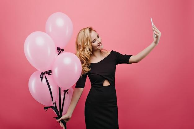 Mulher jovem branca satisfeita usando telefone para selfie em seu aniversário. foto de sorridente senhora romântica segurando um monte de balões de festa rosa.