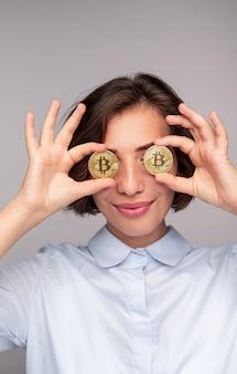 Mulher jovem brincalhona com camisa, sorrindo e segurando bitcoins perto dos olhos contra um fundo cinza