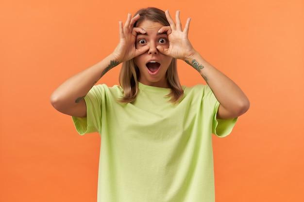 Mulher jovem brincalhona espantada com a boca aberta em uma camiseta amarela olhando para a frente através de óculos feitos por dedos isolados sobre uma parede laranja