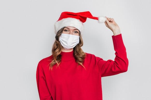Mulher jovem brincalhona feliz com chapéu de papai noel, suéter vermelho e máscara respiratória protetora médica segurando e puxando balabon isolado no fundo cinza do estúdio