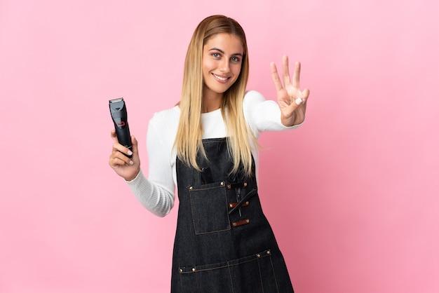 Mulher jovem cabeleireira isolada na parede rosa feliz e contando três com os dedos