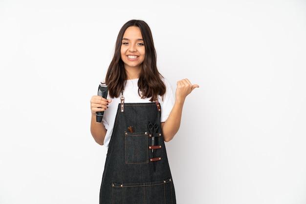 Mulher jovem cabeleireiro isolada no branco apontando para o lado para apresentar um produto