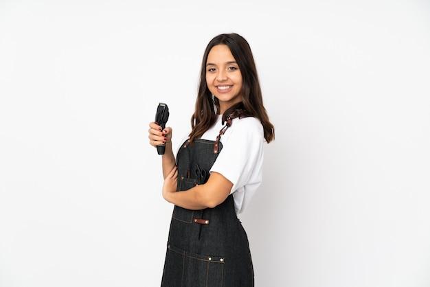 Mulher jovem cabeleireiro na parede branca com os braços cruzados e olhando para a frente