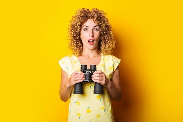 Mulher jovem cacheada surpresa chocada com binóculos na superfície amarela