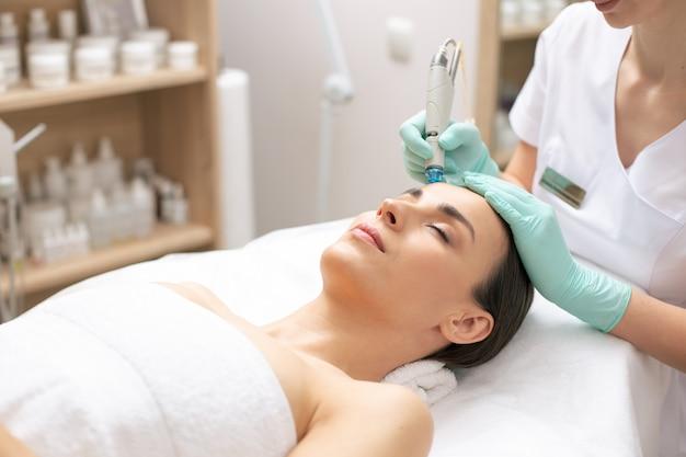 Mulher jovem calma com os olhos fechados enquanto cosmetologista profissional realiza procedimento de dermoabrasão no rosto