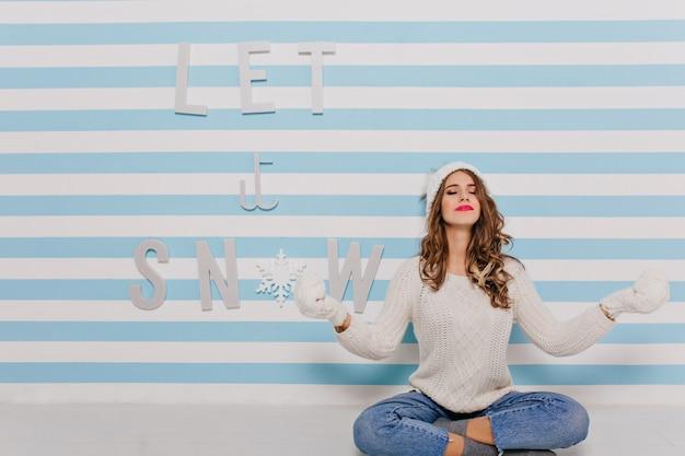 Mulher jovem calma da europa posa, sentada em posição de lótus. garota com suéter de inverno e batom brilhante contra a parede azul